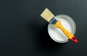 Paint brush placed on top of a can filled with white paint on black background