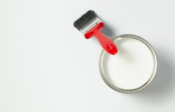 Paint brush and paint bucket filled with white paint