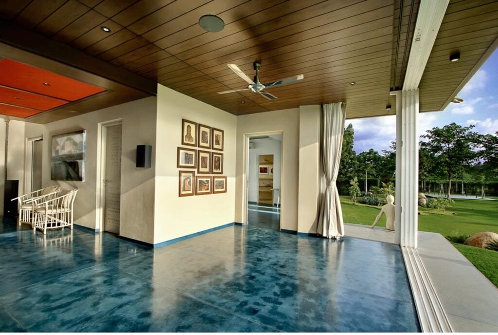 استخدام الخشب الصلب كسقف مستعار، حيث نجد في هذه الغرفة شبه المفتوحة، انفصالًا عن التقاليد مع أرضيات الإيبوكسي الملون المقترنة بالخشب الصلب الداكن على السقف في الأعلى.